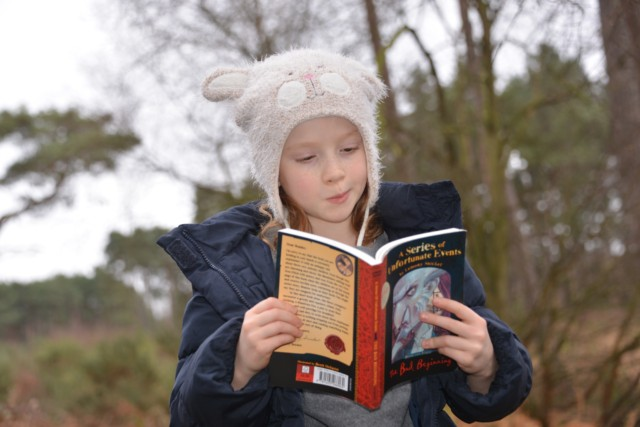 child reading in the forest
