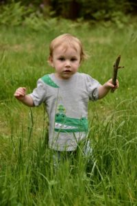 baby in long grass holding a stick