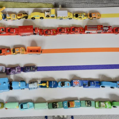 Cars lined up by colour on a sheet of cardboard