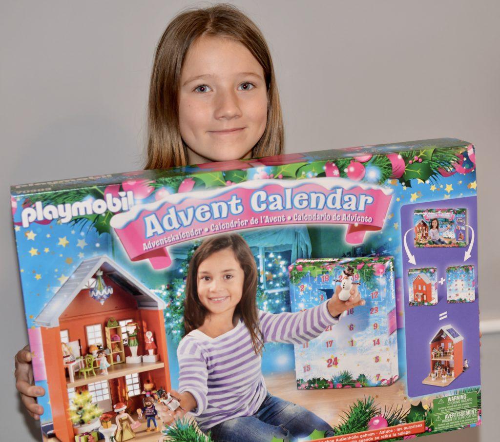 Girl holding Playmobil advent Calendar