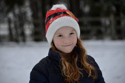 Child in the snow wearing a christmas hat